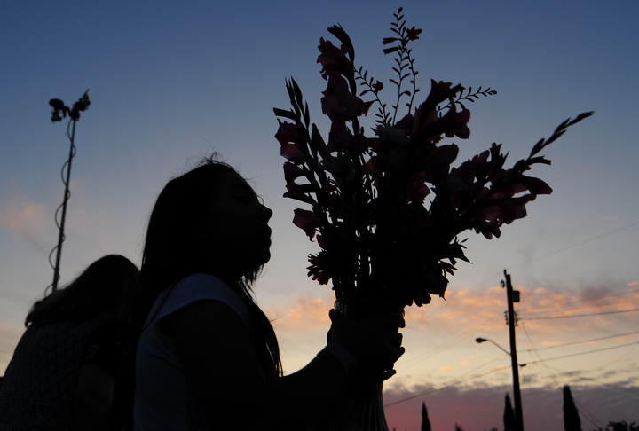 Marité di Flores, 10, walks away with a bouquet of flowers following a candle light vigil for the victim of a stabbing early last week at the South Park Community Center in south Seattle Thursday July 23, 2009. Photo by Daniel Berman/SeattlePI.com