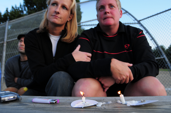 "Angie Dirk, left, and Jennifer Kelley watch a candle light vigil for the victim of a stabbing early last week at the South Park Community Center in south Seattle Thursday July 23, 2009. Kelley played on a softball team with the victim and said ""this affects the larger [Seattle] community, but this community within a community as well."" Added Dirk, ""this really hits close to home for me."" Photo by Daniel Berman/SeattlePI.com"