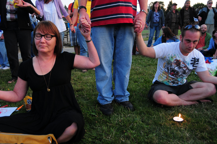Crowd members hold hands during a candle light vigil for the victim of a stabbing early last week at the South Park Community Center in south Seattle Thursday July 23, 2009. Photo by Daniel Berman/SeattlePI.com