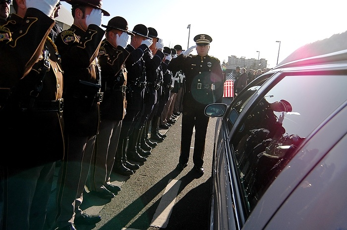 Officers salute the procession during a memorial service for four slain police officers in Tacoma, WA Tuesday December 8, 2009. The memorial brought an estimated 20,000 police officers and community members to the area.