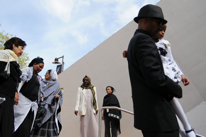 At far right, Abelrahman Shamam enters Key Arena with his daughter, followed by friends and family, before a memorial service for his two children and three other family members killed in an apartment fire Saturday in Fremont.
