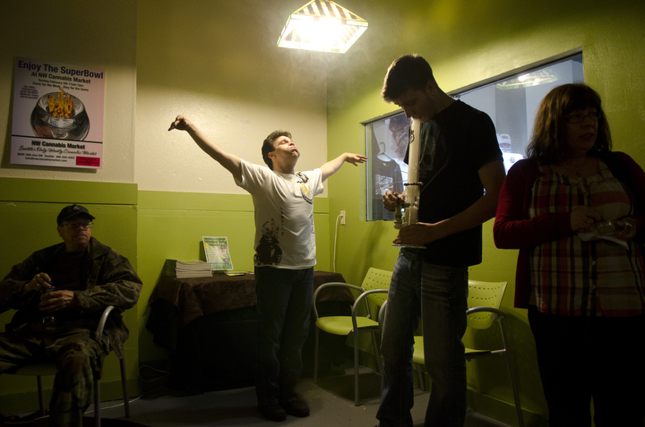 Medical marijuana patients smoke cannabis in the medicating room of the NW Cannabis Market in Seattle, Washington May 22, 2012. A few hundred visit the daily cannabis farmers market, where qualified patients can network with others and obtain medicine, edibles and hardware. Photo by Daniel Berman